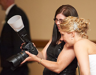 Candid wedding photograph of photographer Heather Potter showing photos to a bride