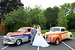 Wedding photograph of a bride and groom with 2 vintage automobiles at the grand olympia