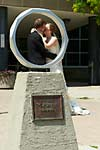 Wedding photograph of a bride and groom kissing behind the iron ring in front of the McMaster University engineering building