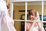 Candid wedding photograph of a bride putting earrings on in the mirror