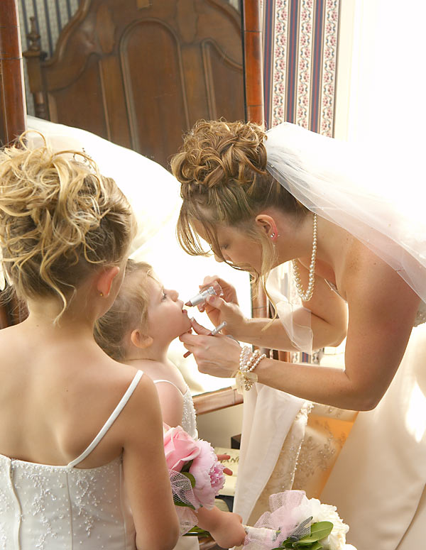 Candid wedding photograph of a bride putting lipstick on her daughter and flower girl