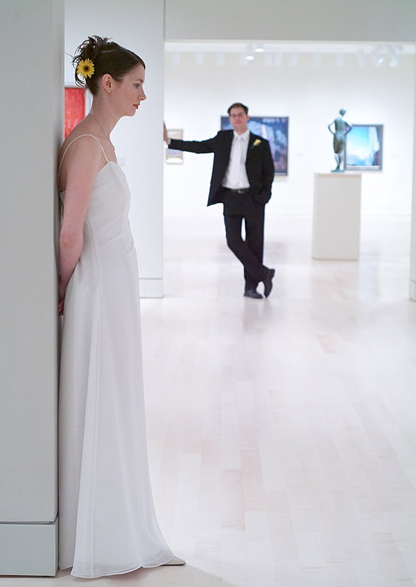 Wedding photograph of a bride daydreaming about her groom at the AGH in Hamilton