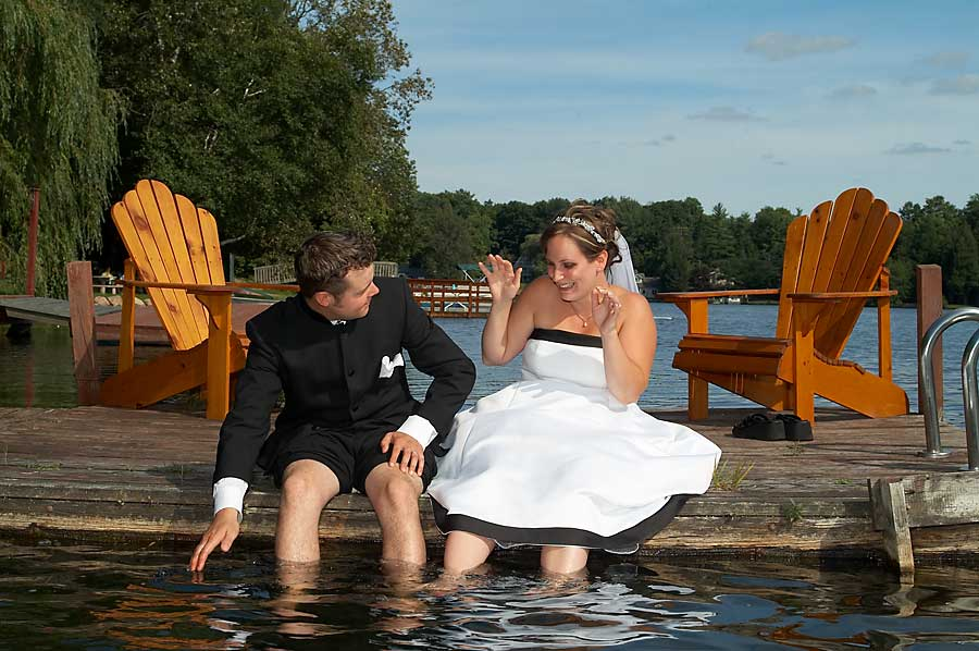 Playful wedding photograph of a bride and groom sitting on a dock with their feet in the water