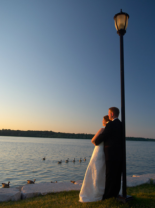 Romantic wedding photograph of a bride and groom near the shore at sunset