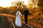 Wedding photograph of a bride and groom walking along train tracks into the sunset with fall colours