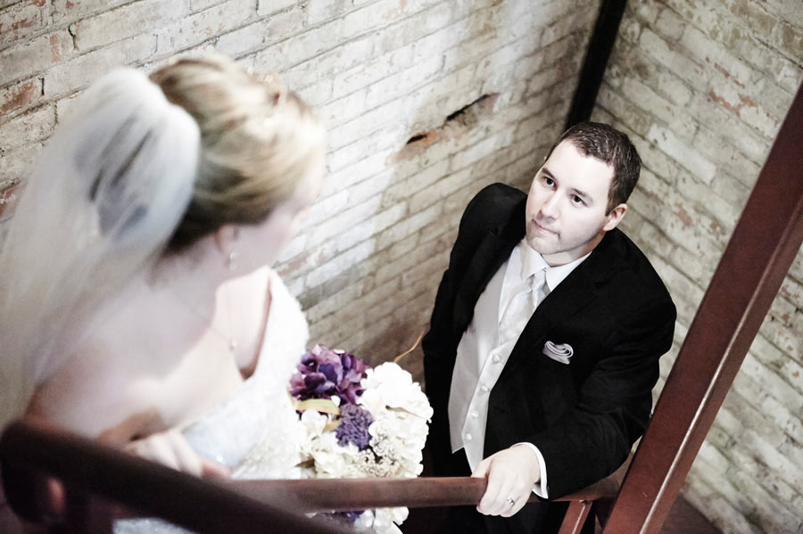Wedding photograph of a groom lovingly gazing at his bride on stairs