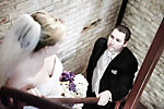 Wedding photograph of a groom gazing at his bride on stairs