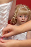Candid wedding photograph of a little flower girl watching the brides dress being laced up